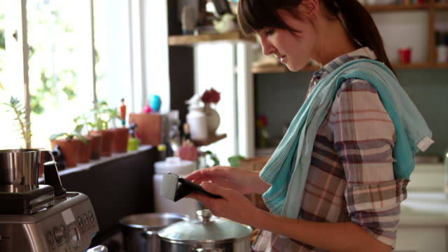 woman in kitchen cooking meal and checking digital tablet - woman cooking stock videos & royalty-free footage