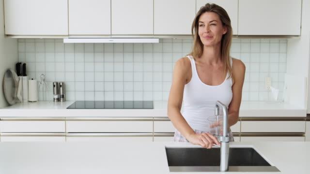 kvinna i köket med kran - looking inside inside cabinet bildbanksvideor och videomaterial från bakom kulisserna
