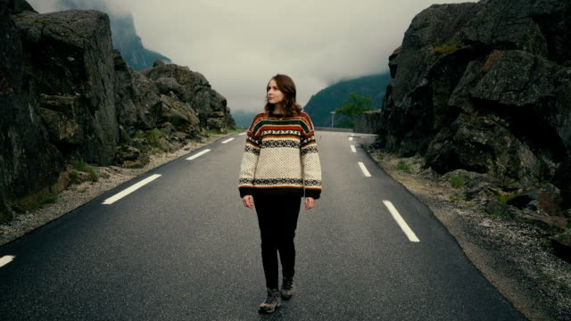 Woman in knitted sweater walking on road in mountains in Norway video