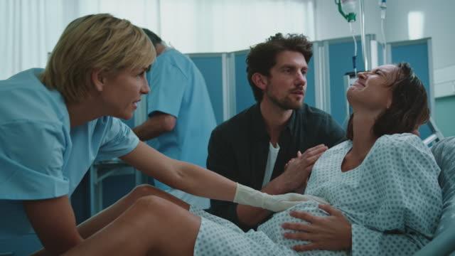 woman in labor with husband and doctor at hospital - mąż filmów i materiałów b-roll