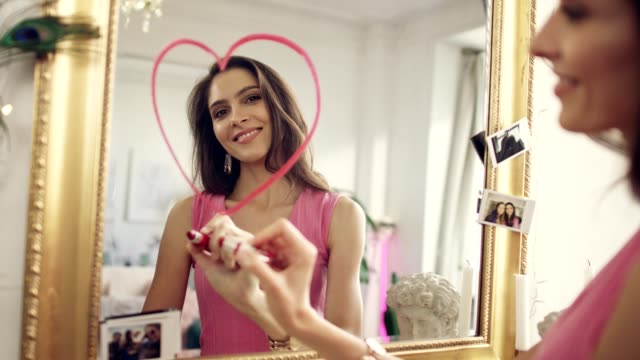 Woman in love. Drawing lipstick heart on a mirror