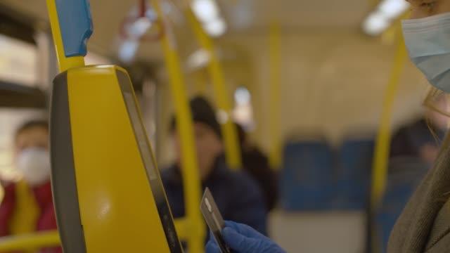donna in maschera e guanti che paga in autobus - fare video stock e b–roll