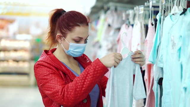 Woman in mask buying children clothes in department store during pandemic video