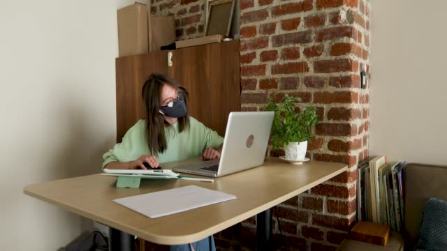 Woman in mask working at night using laptop