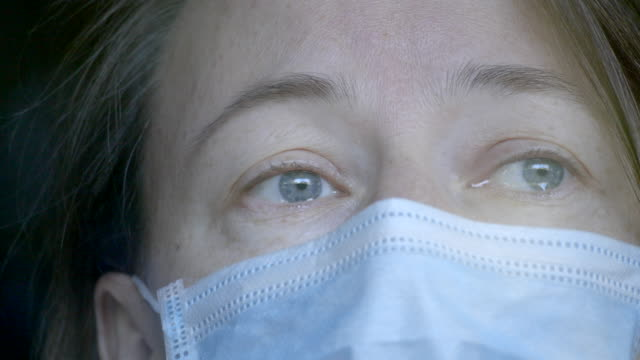 Woman in medical mask looking through the window and crying. video