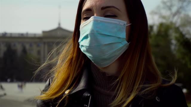 Kvinna i medicinsk skyddsmask går snabbt förbi torget och ängsligt ser sig omkring under karantän och epidemi av coronavirus video