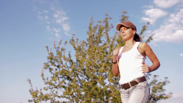 A woman in nature is engaged in fitness with a sports gadget. A woman in nature is engaged in fitness with a sports gadget. panting stock videos & royalty-free footage