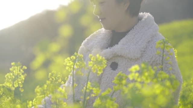 SLOW-MOTION woman in Oilseed rape field