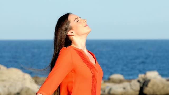 kvinna i orange andas frisk luft på stranden - kvinna tillfreds bildbanksvideor och videomaterial från bakom kulisserna