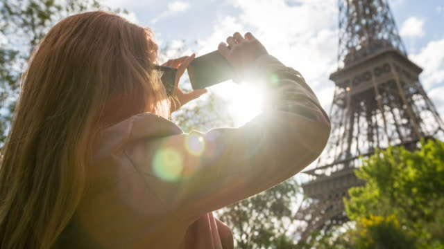 Woman in Paris photographing Eiffel Tower with smartphone
