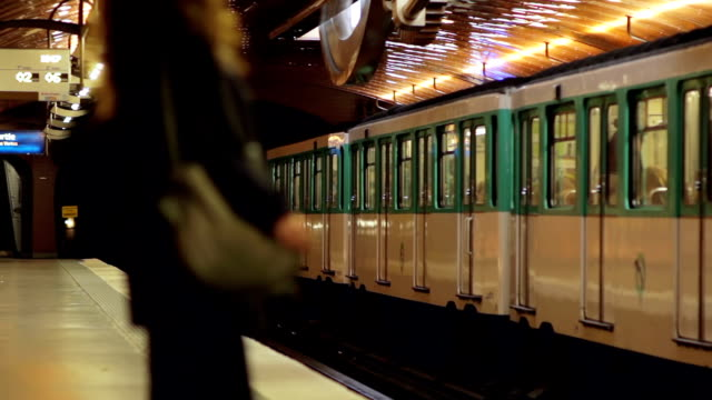 Woman in Parisian metro station Out of focus woman waiting in a metro station as the opposite train departs, Paris, France. subway train stock videos & royalty-free footage