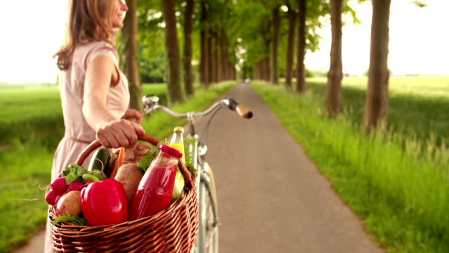 Woman in park with bicycle and basket of vegetables video
