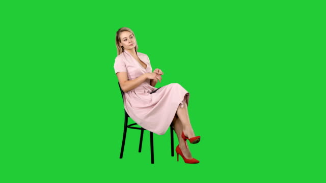 Woman in pink dress sitting on a chair waiting for someone on a Green Screen, Chroma Key Woman in pink dress sitting on a chair waiting for someone on a Green Screen, Chroma Key. Professional shot in 4K resolution. 005. You can use it e.g. in your commercial video, business, presentation, broadcast interview event stock videos & royalty-free footage