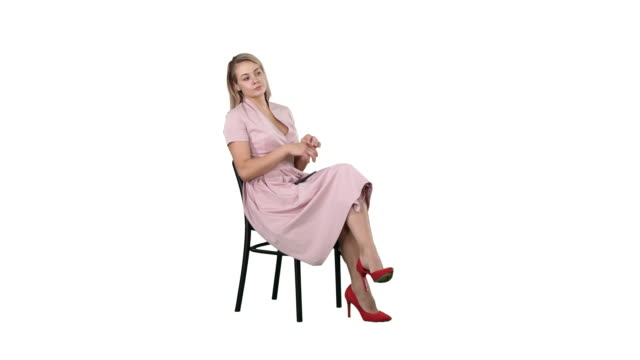 Woman in pink dress sitting on a chair waiting for someone on white background