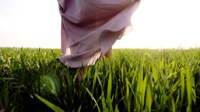 woman in pink dress walks barefoot on grass - scalzo video stock e b–roll
