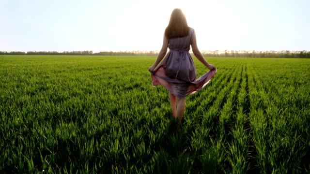 Woman in pink dress walks barefoot on green field video