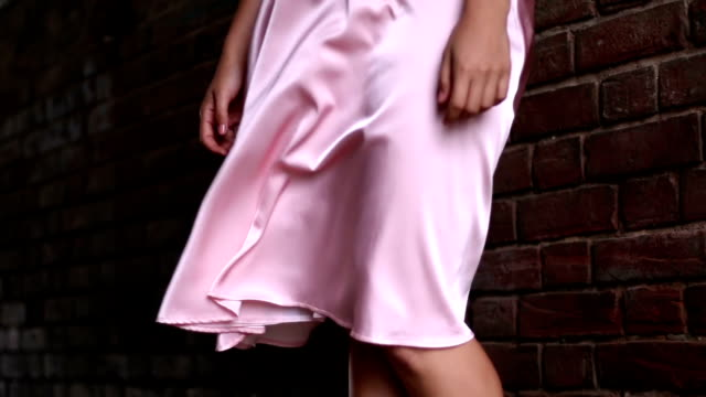 vídeos de stock e filmes b-roll de woman in pink dress with billowing skirt, stands near the brick wall. - saia