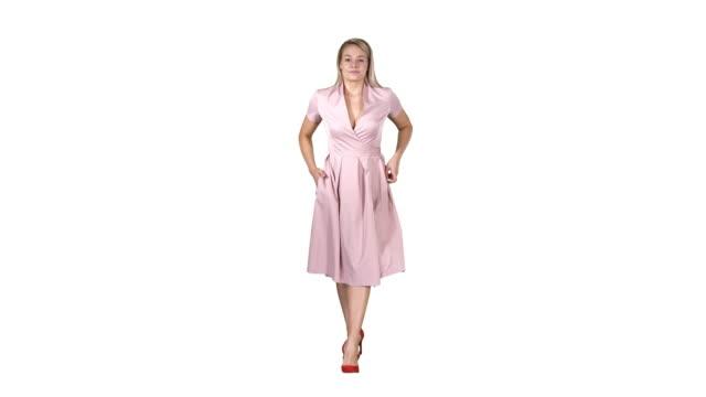 ポケットに手でピンクのドレスの女性は白い背景にカメラの方に歩いています - スタイリッシュ点の映像素材/bロール