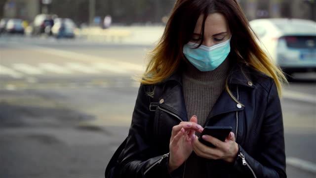 Kvinna i skyddande ansiktsmask skriva meddelanden på mobiltelefon mitt på torget medan korona viruspandemi började video