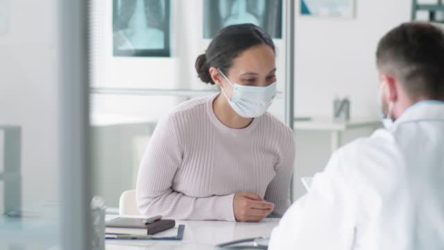 koruyucu maskeli kadın tıp ofisine giriyor ve doktorla konuşuyor - ziyaret stok videoları ve detay görüntü çekimi