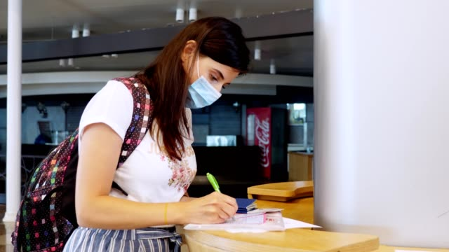 woman in protective mask, holding passport and tickets, fills out documents, medical questionnaire at the airport. new rules and restrictions after coronavirus epidemic end. Resumption of flights, open borders
