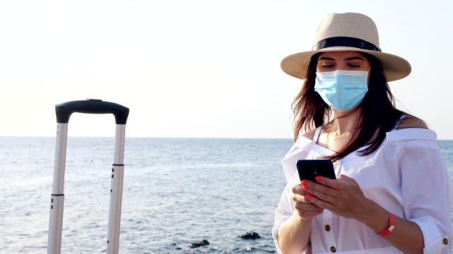 woman in protective mask, summer clothes, sunglasses, sun hat and with travel suitcase, luggage, uses mobile on the seashore. Travelling after Covid-19. the end of self-isolation video