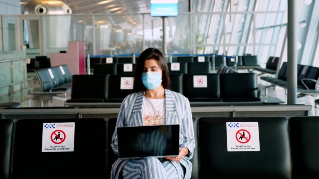 vídeos de stock e filmes b-roll de woman, in protective mask, uses laptop, while sitting in empty airport lounge, waiting to board a flight. air travel re-opened after coronavirus outbreak end. opening borders. travel open - covid flight