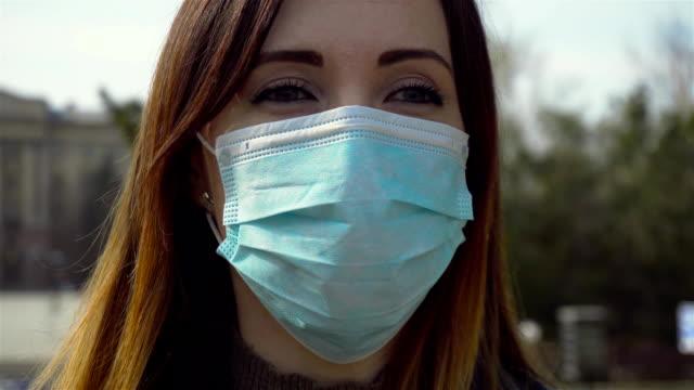Kvinna i skyddande medicinsk mask tar djupa tunga andetag och står mitt i staden video