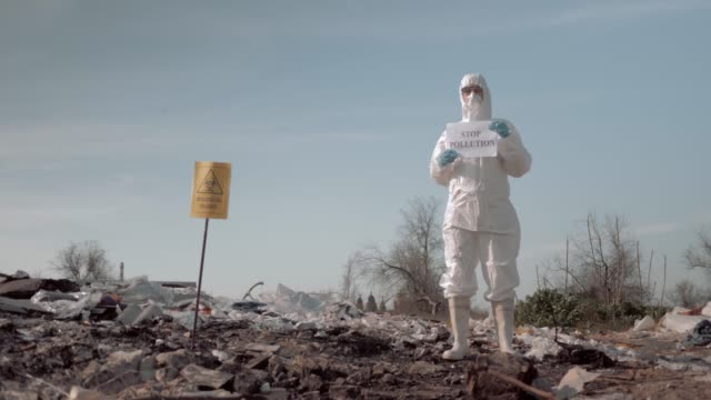woman in protective suit and mask holding poster with stop pollution slogan at garbage dump near sign biological hazard