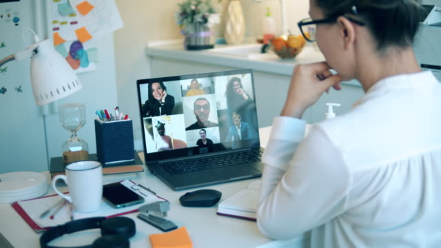 A woman in quarantine is taking part in an online conference video