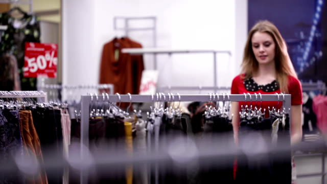 Woman in red dress chooses trousers in clothing store video