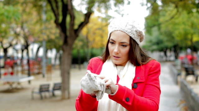 woman in red getting cold and putting gloves - giacca video stock e b–roll