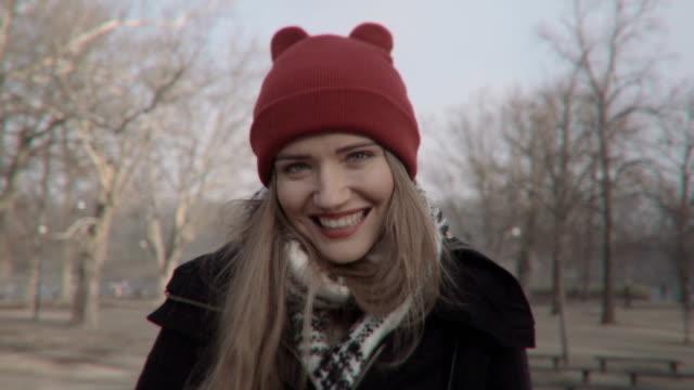 Femme dans un chapeau rouge à la recherche dans la caméra et souriant, en plein air. - Vidéo