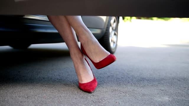 vídeos de stock, filmes e b-roll de mulher de salto alto vermelho em carro estacionado - perna termo anatômico