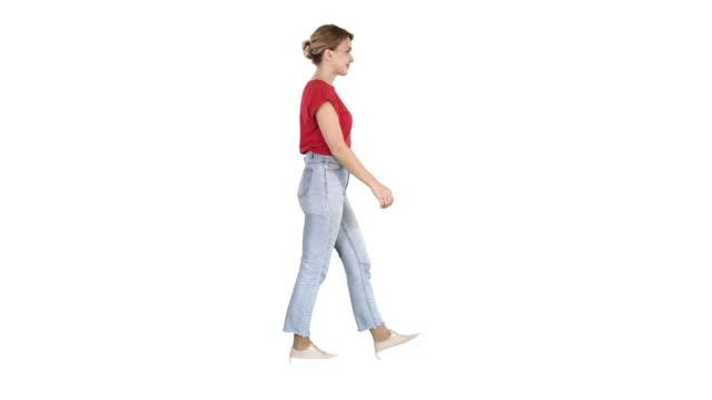 白い背景の上を歩く赤い t シャツ、ジーンズとスニーカーの女性 - 全身点の映像素材/bロール