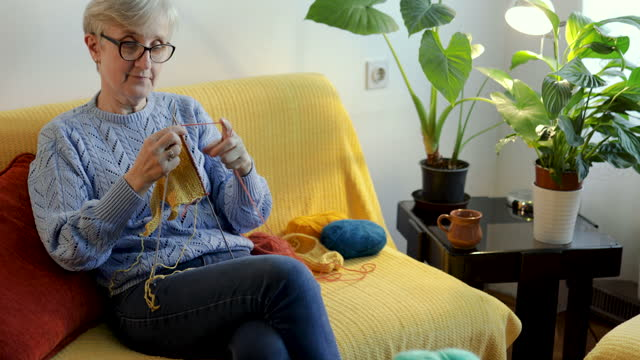 Woman in retirement knitting a swatter in her living room