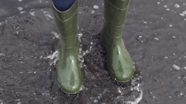 A woman in rubber boots jumping over a puddle. Slow motion video