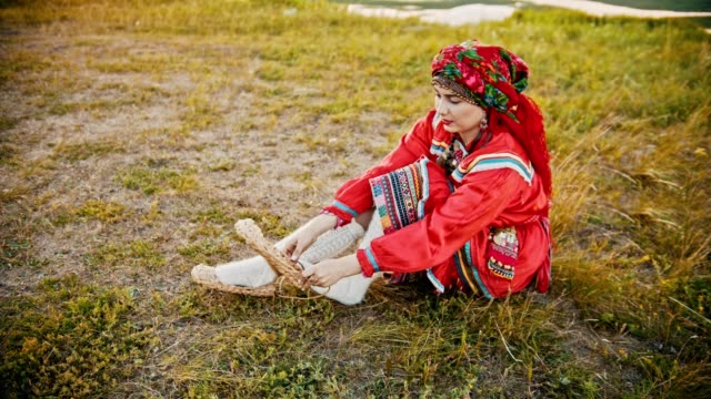 a woman in russian folk clothes putting on bast shoes - sitting on the field. - славянская культура стоковые видео и кадры b-roll
