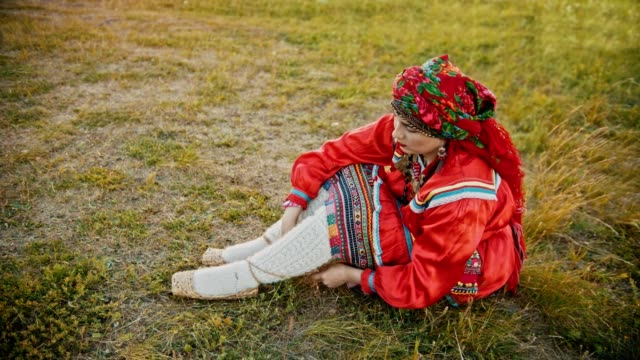 a woman in russian red folk clothes putting on bast shoes - sitting on the field. - славянская культура стоковые видео и кадры b-roll