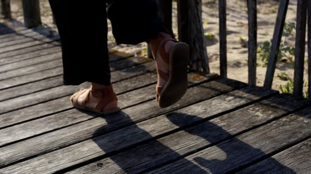 Woman in sandals walking to the beach, in Portugal