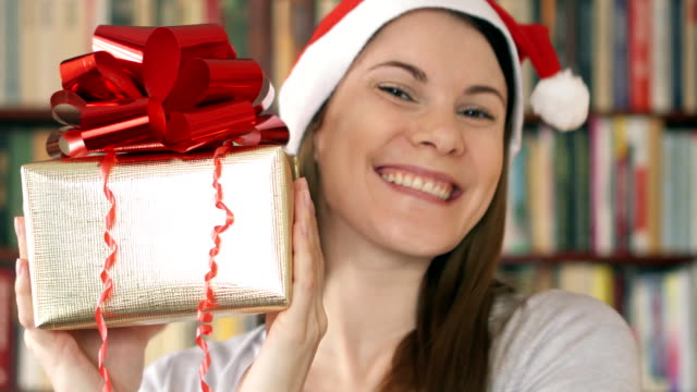 Woman in Santa's hat with present. Female with golden gift box with red ribbon celebrating Christmas video