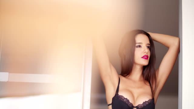 woman in sexy lingerie is standing in door of balcony video