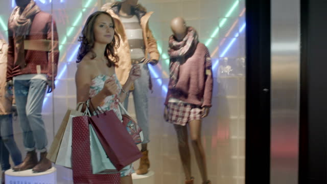 Woman in shopping center with bags. Fashion girl in mall looking on shopwindow background