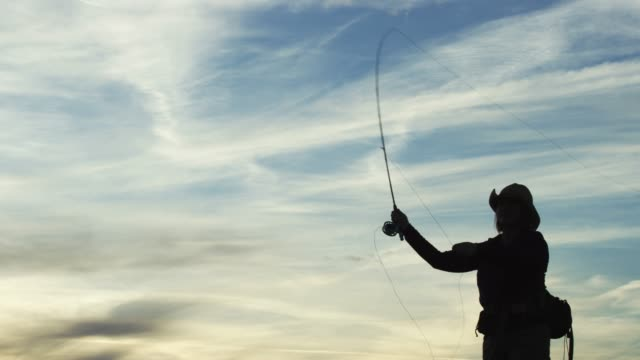 A Woman in Silhouette Fly Fishes at Sunset Under a Partly Cloudy Sky A Woman in Silhouette Fly Fishes at Sunset Under a Partly Cloudy Sky fishing rod stock videos & royalty-free footage