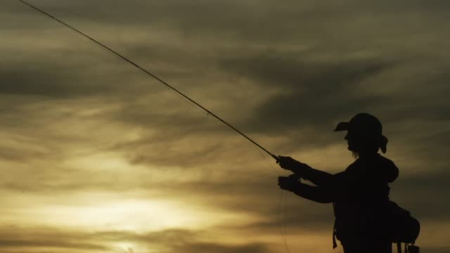 a woman in silhouette fly fishes at sunset under a partly cloudy sky - fishing video stock e b–roll
