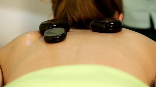 frau in spa-salon mit massage mit warmen steinen - la stone therapie stock-videos und b-roll-filmmaterial