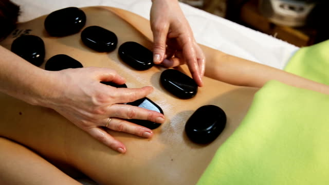 frau in spa-salon mit massage mit warmen steinen - alternative medizin stock-videos und b-roll-filmmaterial