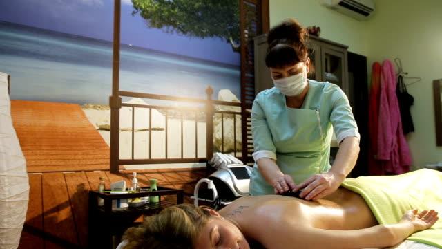 kobieta w spa salon z gorących kamieni - terapia lastone filmów i materiałów b-roll