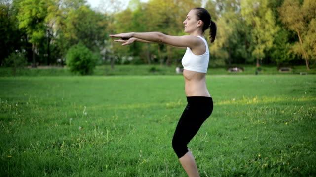 vídeos de stock e filmes b-roll de mulher no desporto conjunto de fazer um exercício de agachamento - agachar se