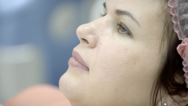 Woman in sterile cap quietly waiting for procedure for beauty video